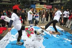 【重庆商报】大学生行为艺术宣传环保:碳足迹留白布
